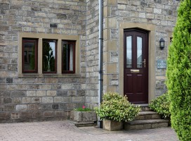 Shaped Harlech composite door in Rosewood with Prairie glass.